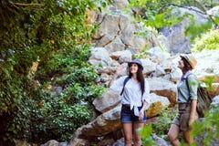 Två härliga unga flickor reser i bergen och tycker om sikten av landskapet av gröna träd Royaltyfria Foton