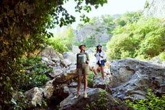 Två härliga unga flickor reser i bergen och tycker om sikten av landskapet av gröna träd Royaltyfria Bilder