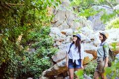 Två härliga unga flickor reser i bergen och tycker om sikten av landskapet av gröna träd Arkivfoto