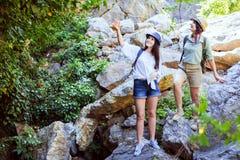 Två härliga unga flickor reser i bergen och tycker om sikten av landskapet av gröna träd Arkivfoton