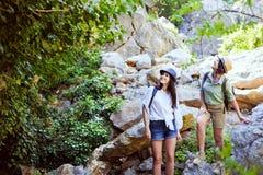 Två härliga unga flickor reser i bergen och tycker om sikten av landskapet av gröna träd Royaltyfri Fotografi