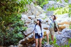 Två härliga unga flickor reser i bergen och tycker om sikten av landskapet av gröna träd Royaltyfri Bild