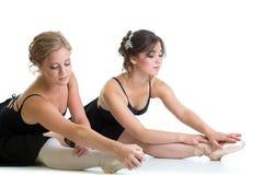 Två härliga unga flickor som gör sträckning av övning eller av splittringar arkivbild