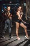 Två härliga unga konditionflickor som poserar med sportutrustning i idrottshall posera med skivstången Arkivbilder