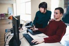 Två härliga unga kontorsarbetare som ser en dator, övervakar och diskuterar projektet Läget i kontoret royaltyfria bilder