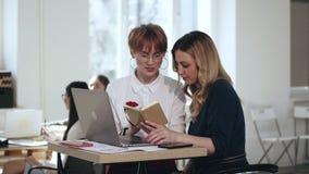 Två härliga unga kvinnliga chefer som arbetar samman med bärbara datorn och notepaden, diskuterar arbete på den moderna vindkonto arkivfilmer