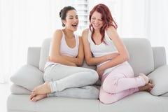 Två härliga unga kvinnliga vänner som skrattar i vardagsrum Fotografering för Bildbyråer