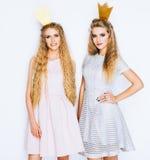 Två härliga unga kvinnor firar möhippan på vit bakgrund Bästa vän som bär på den stilfulla aftonklänningen, krona royaltyfria foton