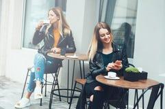 Två härliga unga kvinnor i innegrej bär att sitta som är utomhus- i kafé, och att använda smartphones, medan dricka kaffe Affärsm fotografering för bildbyråer