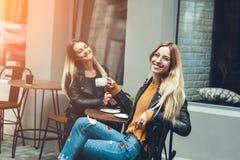 Två härliga unga kvinnor i modekläder som har, vilar samtal och att dricka av kaffe i den utomhus- restaurangen royaltyfri foto