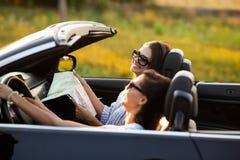 Två härliga unga kvinnor i solglasögon sitter i en svart cabriolet och ler på en solig dag Ett av dem uppehällen royaltyfri foto