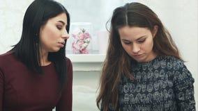 Två härliga unga kvinnor med tidskriften i vardagsrumsamtalet stock video