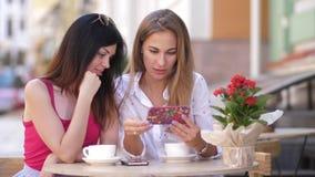 Två härliga unga kvinnor sitter på tabellen i kafé och ser i telefonen 4K långsam rörelse lager videofilmer