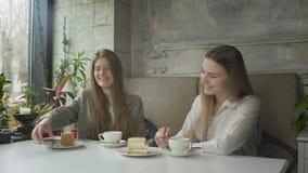 Två härliga unga kvinnor som dricker kaffe och äter kakor på kafét arkivfilmer