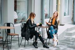 Två härliga unga kvinnor som dricker te och skvallrar i den utomhus- trevliga restaurangen royaltyfri fotografi