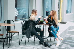Två härliga unga kvinnor som dricker te och skvallrar i den utomhus- trevliga restaurangen royaltyfria bilder