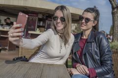 Två härliga unga kvinnor som har rolig det fria, medan genom att använda deras mobiltelefoner som tar selfie royaltyfri foto