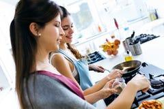 Två härliga unga kvinnor som lagar mat och tillfogar peppar till grönsaker Royaltyfri Bild