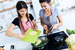 Två härliga unga kvinnor som tillfogar potatisar till chardsna in i pannan Royaltyfri Foto