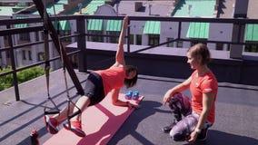 Två härliga unga kvinnor utbildar i den nya luften Utbildning av muskler Flickor håller diagramet stock video