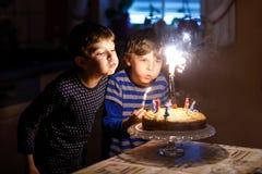 Två härliga ungar, små förskole- pojkar som firar födelsedag och blåser stearinljus royaltyfri bild