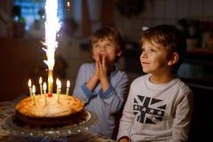 Två härliga ungar, små förskole- pojkar som firar födelsedag och blåser stearinljus royaltyfri fotografi