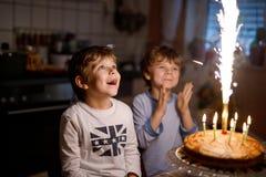 Två härliga ungar, små förskole- pojkar som firar födelsedag och blåser stearinljus Arkivbild