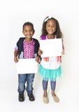 Två hållande övre för gulliga ungar ett tomt tecken Royaltyfri Fotografi