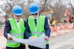 Två höga arkitekter eller affärspartners som arbetar på en konstruktionsplats under kontroll som ser ritningar arkivfoto
