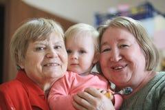 Två höga kvinnor - farmödrar med behandla som ett barn flickatodler arkivfoton
