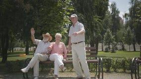 Två höga män och vinkande händer för en kvinna i parkerar Moget folk som vilar det fria, aktiv livsstil gladlynt pension?r arkivfilmer