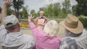 Två höga män och vinkande händer för en kvinna, medan den fjärde kvinnan som tar ett foto av dem i, parkerar Moget folk stock video