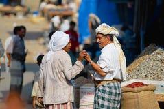 Två höga män talar på gatamarknaden i Sanaa, Yemen Arkivbild