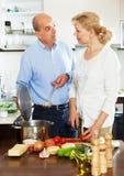 Två höga personer som lagar mat i köket Royaltyfri Foto