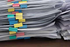 Två högar av dokument med färgrika gem på skrivbordet Arkivfoto
