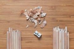 Två högar av träblyertspennor Blyertspennan som vässar process Arkivbilder