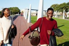 Två högskolavänner som skrattar ha bra tid arkivfoton