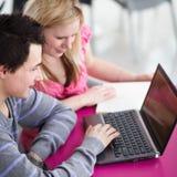 Två högskolestudenter som har gyckel studera tillsammans Arkivfoto