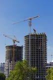 Konstruktionsplats med kranar och byggnader. Fotografering för Bildbyråer