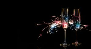 Två högväxta exponeringsglas av champagne i mångfärgade Bengal ljus Arkivbilder