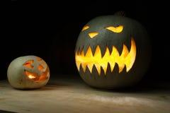 Två halloween pumpor som är roliga och som är spöklika på den wood tabellen Arkivbilder