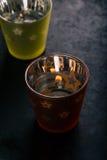 Två halva genomskinliga koppar med stearinljuset inom Royaltyfri Bild