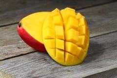 Två halvor av den röda mango på trätabellen Arkivfoton
