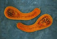 Två halvor av enformad pumpa av orange färg, lokaliseras mot turkosfärg arkivfoton