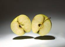 Två halvor av ett äpple i luften Fotografering för Bildbyråer