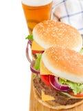 Två hamburgare med öl fotografering för bildbyråer
