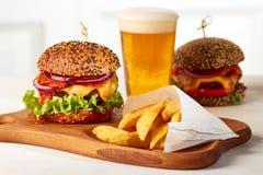 Två hamburgare med franska småfiskar och exponeringsglas av öl arkivbilder