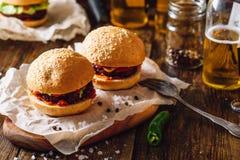 Två hamburgare och ölflaskor royaltyfri bild