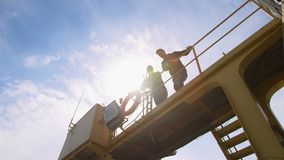 Två hamnarbetare, coworkers och colleages ser kameran och räcker att vinka på en industriell hamn arkivfilmer