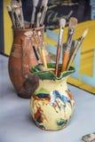 Två hand-gjorde keramiska behållare fulla av konstmålarfärgborstar som sitter på vit yttersida med färg som blockerar bak - selek royaltyfri bild